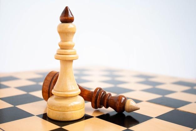 Op de voorgrond staat een witte koning op het schaakbord en een zwarte koning ligt ernaast