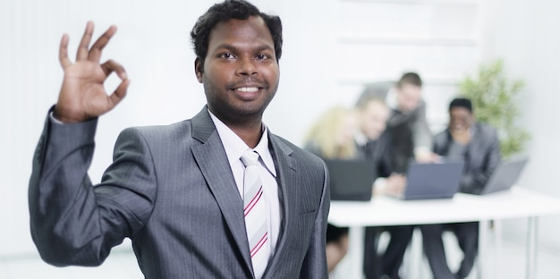 Op de voorgrond toont een jonge zakenman gebaar ok, staande in het kantoor