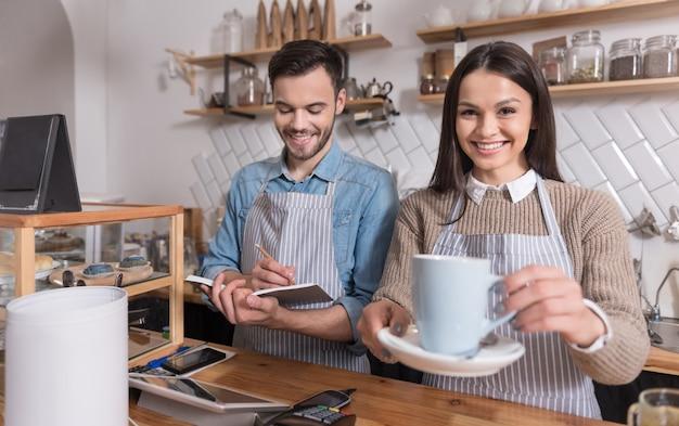 Op de werkplek. tevreden emotionele obers die glimlachen en koffie verkopen terwijl ze aan het loket staan