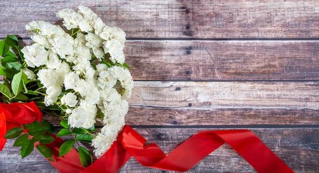 Op donkere planken ligt een boeket witte rozen met een rood lint.