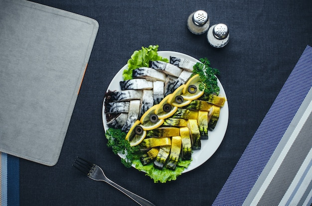 Op donkere stoffen, op het bord is een prachtige vis, haring en zalm versierd met groen