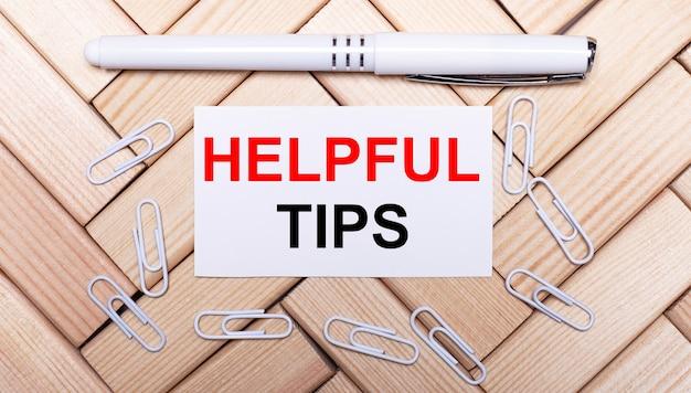Op een achtergrond van houten blokken, een witte pen, witte paperclips en een witte kaart met de tekst nuttige tips