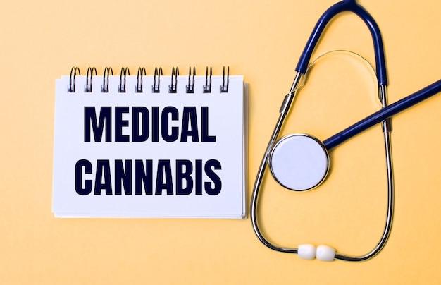 Op een beige achtergrond, een stethoscoop en een wit notitieblok met de inscriptie medical cannabis