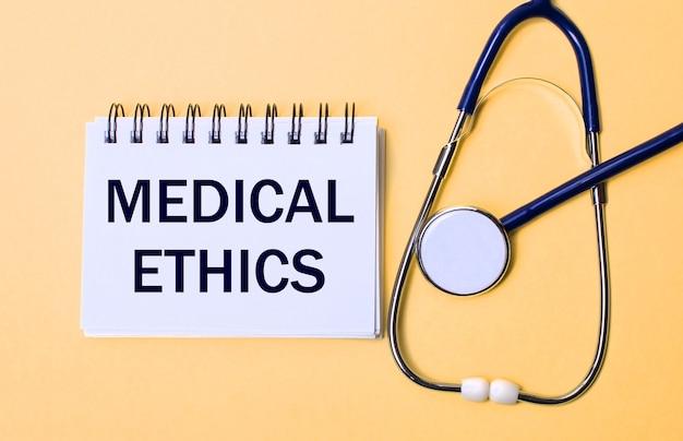 Op een beige achtergrond, een stethoscoop en een wit notitieblok met de inscriptie medical ethics. medisch concept