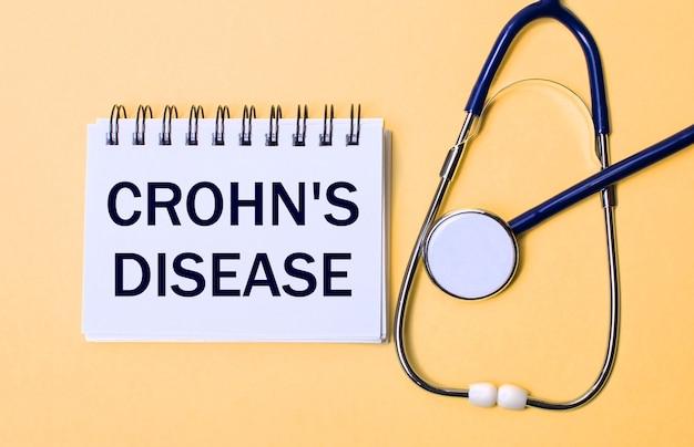 Op een beige achtergrond, een stethoscoop en een wit notitieblok met het opschrift crohn is ziekte. medisch concept
