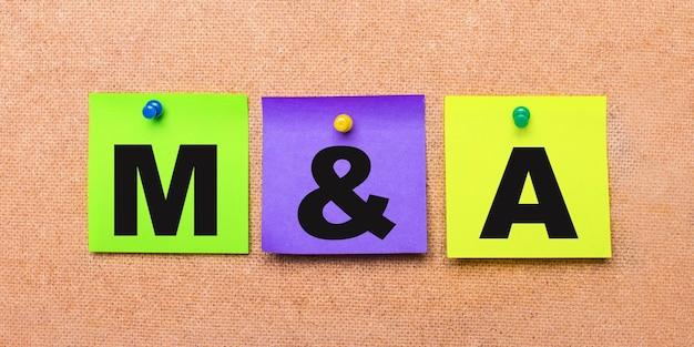 Op een beige achtergrond, veelkleurige stickers voor notities met het woord m en a