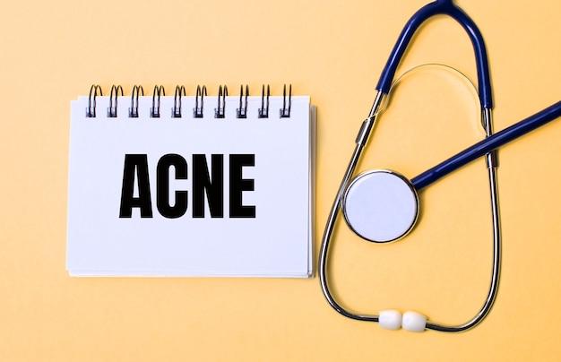 Op een beige muur, een stethoscoop en een wit notitieblok met de inscriptie acne. medisch concept