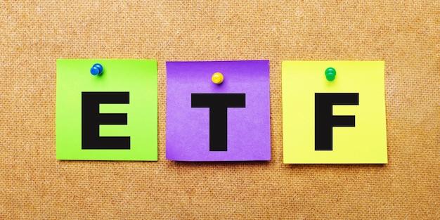 Op een beige ondergrond, veelkleurige stickers voor bankbiljetten met het woord etf exchange traded funds