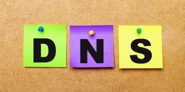 Op een beige tafel, veelkleurige stickers voor notities met het woord dns domain name system