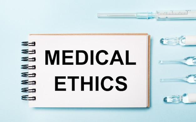 Op een blauwe achtergrond ampul met medicijnen en een notitieboekje met de tekst medical ethics