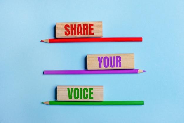 Op een blauwe achtergrond, drie kleurpotloden, drie houten blokken met tekst share your voice