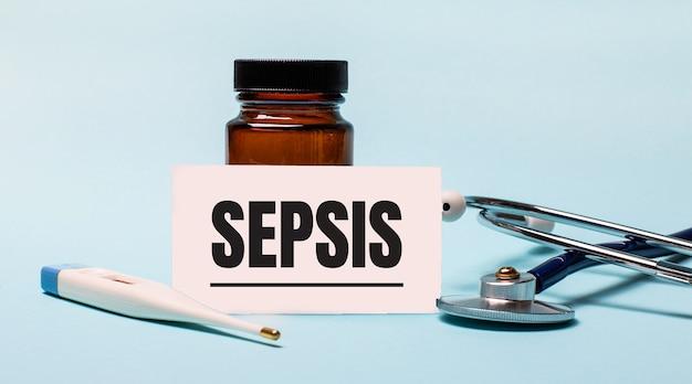 Op een blauwe achtergrond - een fles voor pillen, een stethoscoop, een elektronische thermometer en een kaart met het opschrift sepsis. medisch concept