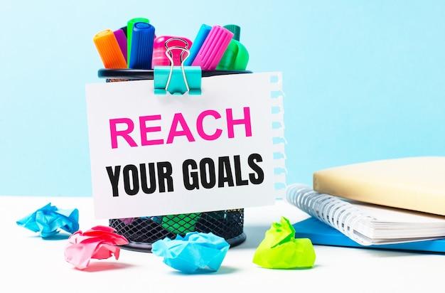 Op een blauwe achtergrond - een standaard met heldere markeringen, blocnotes en veelkleurige verfrommelde stukjes papier. een vel papier met de tekst reach your goals.