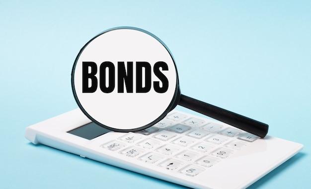 Op een blauwe achtergrond een witte rekenmachine en een vergrootglas met de tekst bonds. bedrijfsconcept