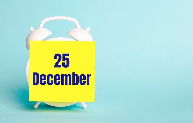 Op een blauwe achtergrond - een witte wekker met een gele sticker voor notities met de tekst december 25