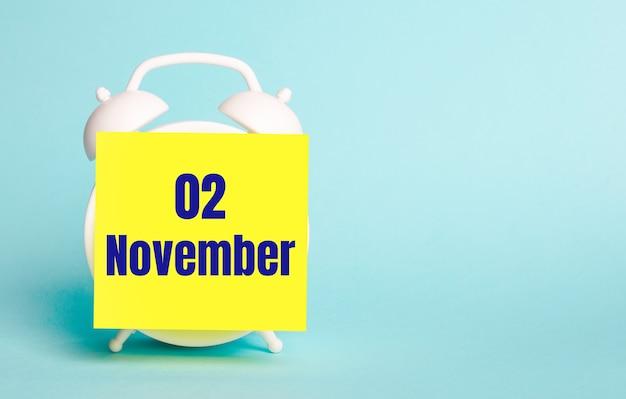 Op een blauwe achtergrond - een witte wekker met een gele sticker voor notities met de tekst november 02