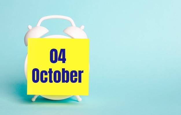 Op een blauwe achtergrond - een witte wekker met een gele sticker voor notities met de tekst oktober 04