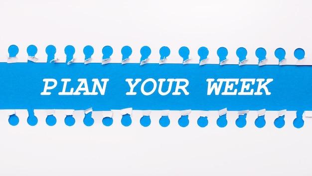 Op een blauwe achtergrond met tekst plan your week twee witte gescheurde stroken papier.