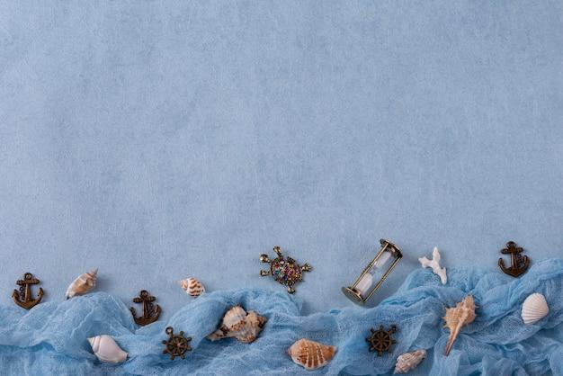 Op een blauwe achtergrond, objecten met mariene thema's: schelpen, schildpad, sandclock