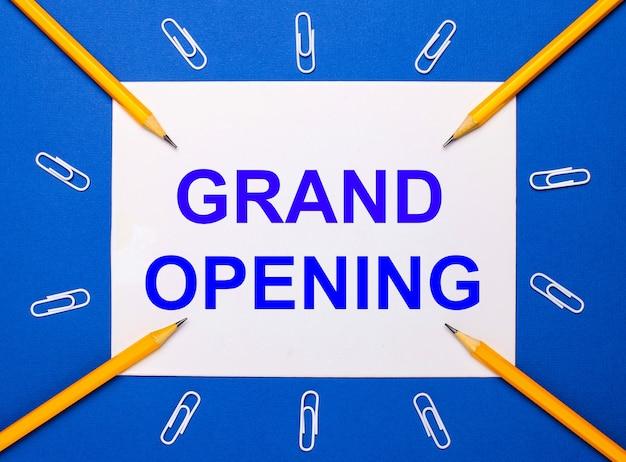 Op een blauwe achtergrond, witte paperclips, gele potloden en een wit vel papier met de tekst grand opening