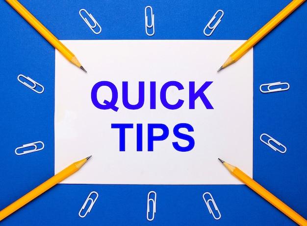 Op een blauwe achtergrond, witte paperclips, gele potloden en een wit vel papier met de tekst quick tips
