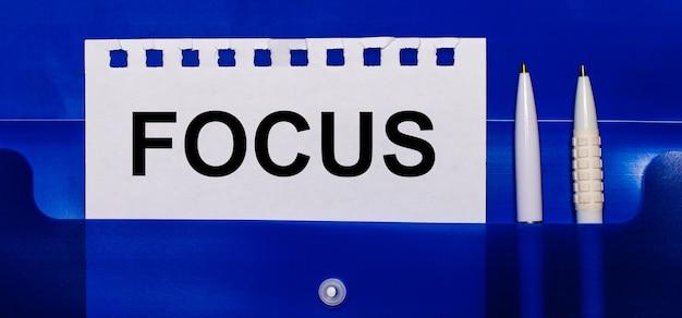 Op een blauwe achtergrond, witte pennen en een vel papier met de tekst focus