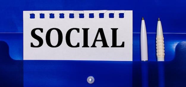 Op een blauwe achtergrond, witte pennen en een vel papier met de tekst social