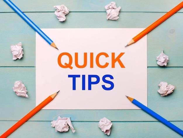 Op een blauwe achtergrond - zwarte en oranje potloden, witte verfrommelde vellen papier en een wit vel papier met de tekst quick tips