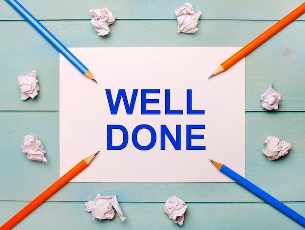 Op een blauwe achtergrond - zwarte en oranje potloden, witte verfrommelde vellen papier en een wit vel papier met de tekst well done