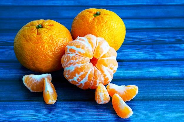 Op een blauwe houten tafel. mandarijnen in de huid en zonder de huid. plakken van gepelde mandarijn. citrus vruchten