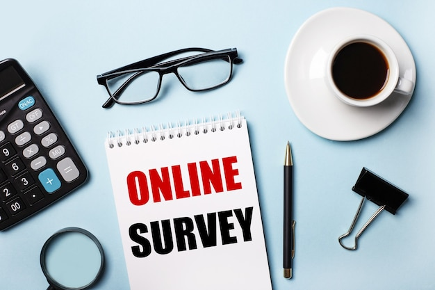 Op een blauwe tafel, bril, rekenmachine, koffie, vergrootglas, pen en notitieboekje met de tekst online survey
