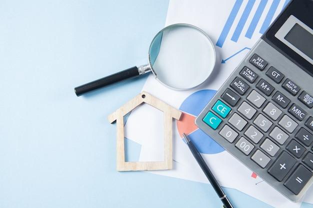 Op een blauwe tafel een rekenmachine, statistieken, een pen en een huis