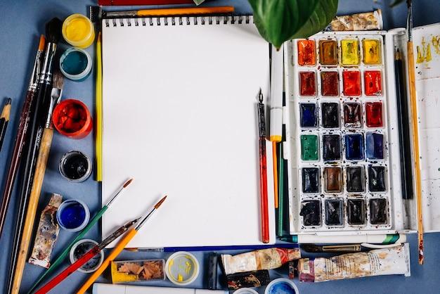 Op een blauwe tafel staan artistieke benodigdheden, wit papier en kleurrijke kleuren