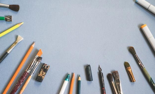 Op een blauwe tafel staan veel kunstpenselen en potloden