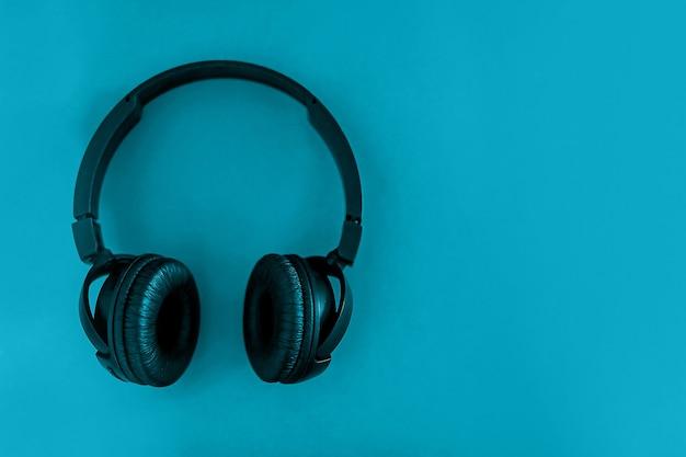 Op een blu-achtergrond staan zwarte koptelefoons. plat leggen.