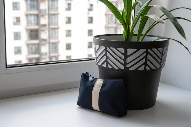 Op een brede witte vensterbank bij het raam staat een grote zwart-witte pot met een groene plant. naast de pot zit een donkerblauw make-uptasje met een witte streep