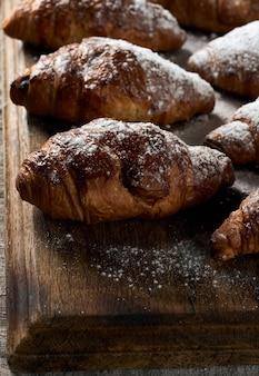 Op een bruin houten bord liggen gebakken croissants bestrooid met poedersuiker