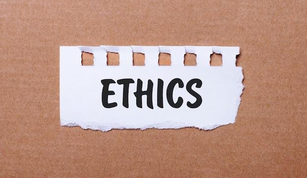 Op een bruin oppervlak, wit papier met de inscriptie ethiek.