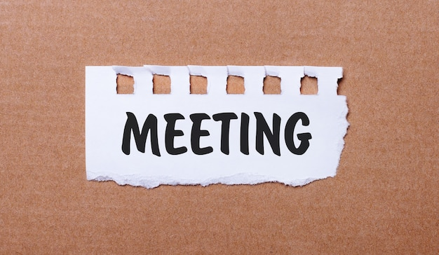 Op een bruine achtergrond, wit papier met de inscriptie meeting