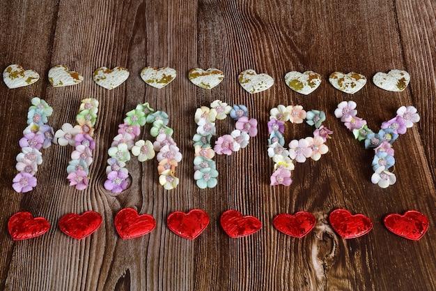 Op een bruine houten ondergrond staat het woord gelukkig in grote letters van veelkleurige bloemen. decoratieve harten zijn boven en onder in een lijn gevoerd