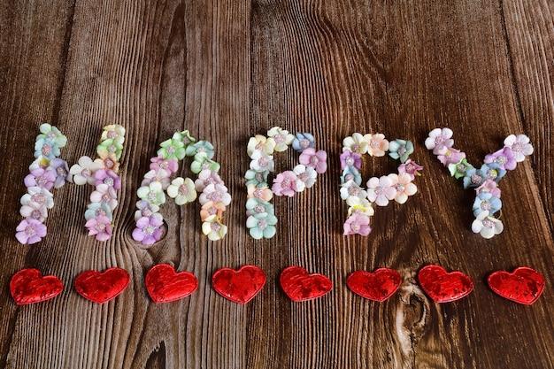Op een bruine houten ondergrond staat het woord gelukkig in grote letters van veelkleurige bloemen. decoratieve harten zijn van onderen in een lijn opgesteld