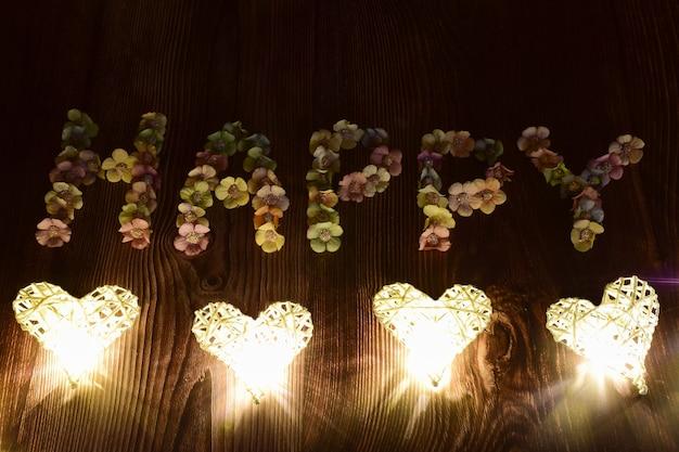 Op een bruine houten ondergrond staat het woord gelukkig in grote letters van veelkleurige bloemen. gloeiende harten zijn van onderen in een lijn gelegd