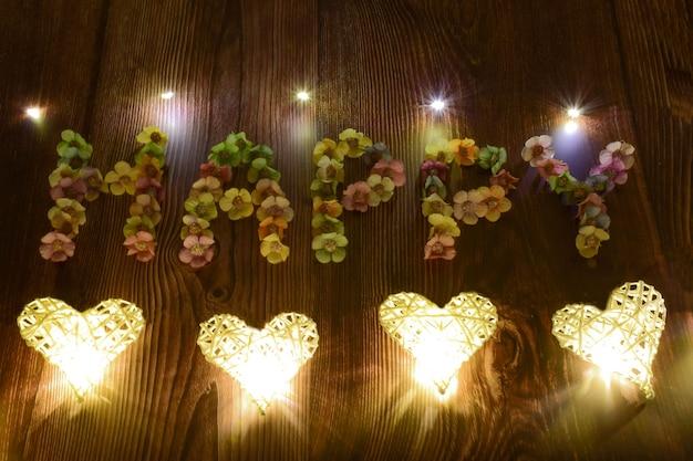 Op een bruine houten ondergrond wordt het woord gelukkig gespeld in grote letters van veelkleurige bloemen