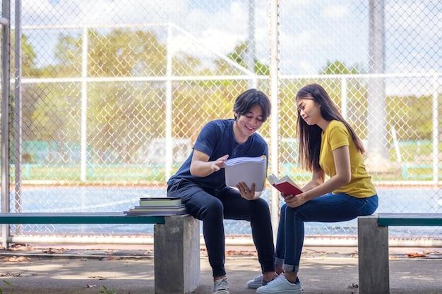Op een campus studeren een paar studenten samen en een tiener zit op een stoel naast een sportveld met een boek.