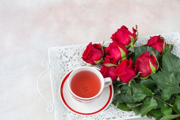 Op een dienblad een boeket rode rozen en een kopje thee