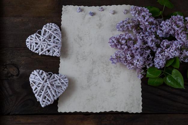 Op een donker houten tafel schrijfpapier, een boeket lila en twee witte harten