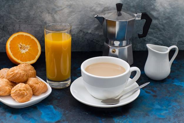 Op een donkere achtergrond koffie met melk, gebak, koffiepot en een glas met sinaasappelsap