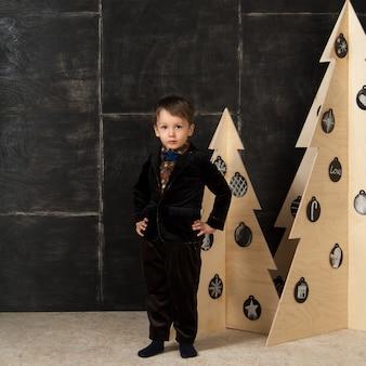 Op een donkere achtergrond poseert kleine jongen in een stijlvol kostuum in de buurt van een kerstboom gemaakt van hout