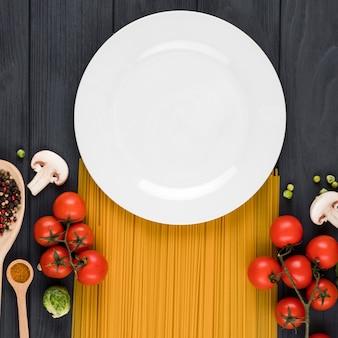 Op een donkere achtergrond staat een bord, pasta, tomaten, kruiden