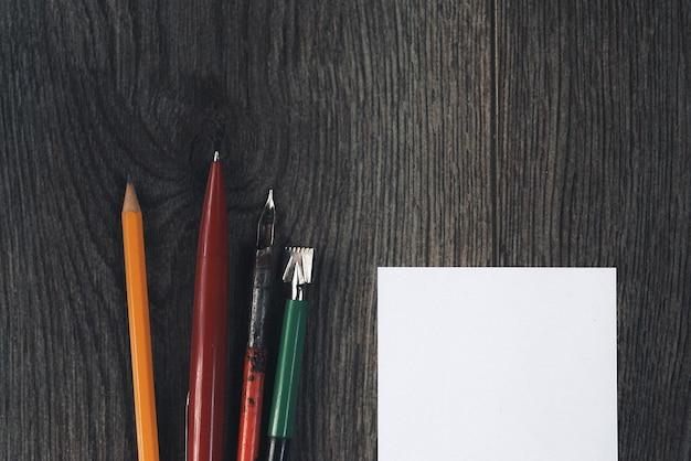Op een donkere houten ondergrond ligt wit papier en pennen